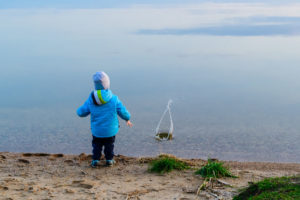 child at the sand beach near the water launched the little ship, the weather is cold, concept of disturbance